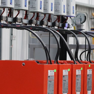 A row of lead acid batteries on charge in a warehouse