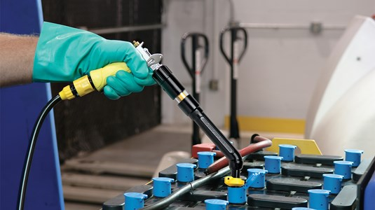 A man using a Philadelphia Scientific Battery Watering Gun to water a lead acid battery